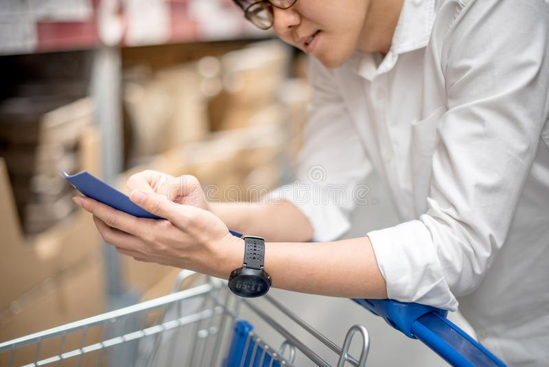 Young Asian man checking the shopping list in warehouse. Young Asian man standing with cart checking the shopping list in warehouse wholesale, shopping stock images