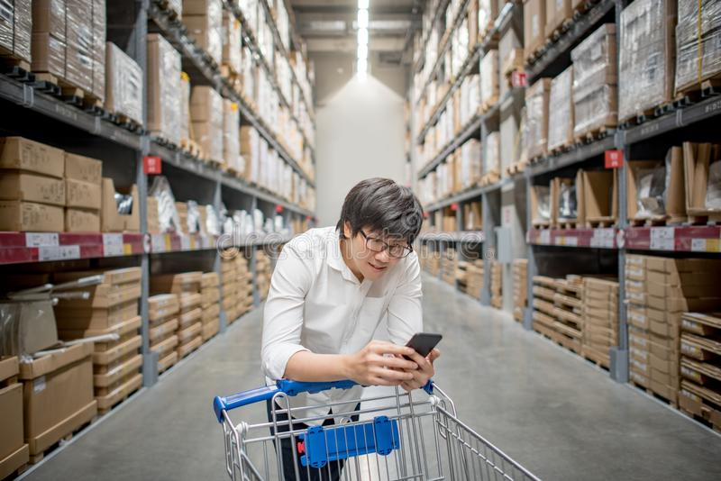 Young Asian man with trolley cart checking the shopping list in. Young Asian man standing with trolley cart checking the shopping list on his smartphone royalty free stock photos