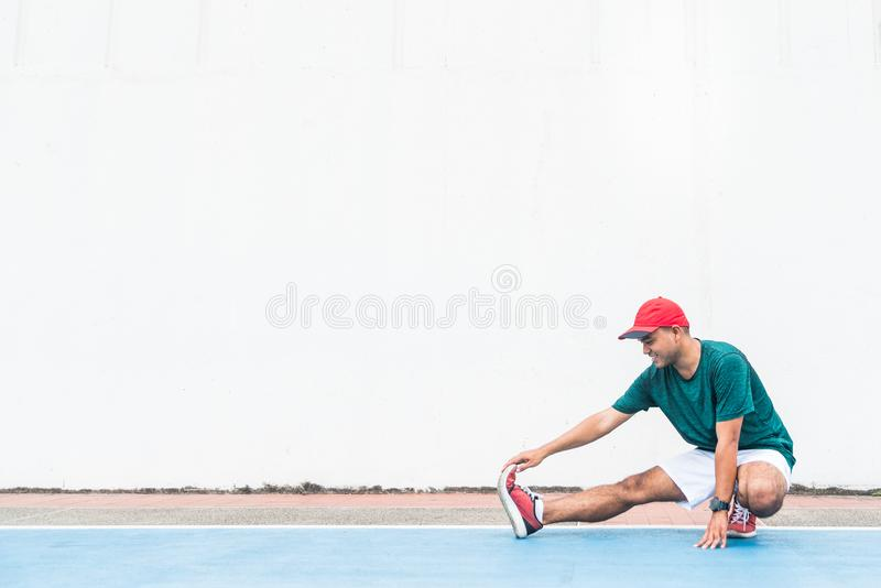 Young asian man stretching legs before run with copy space. Young asian man stretching legs before run stock images