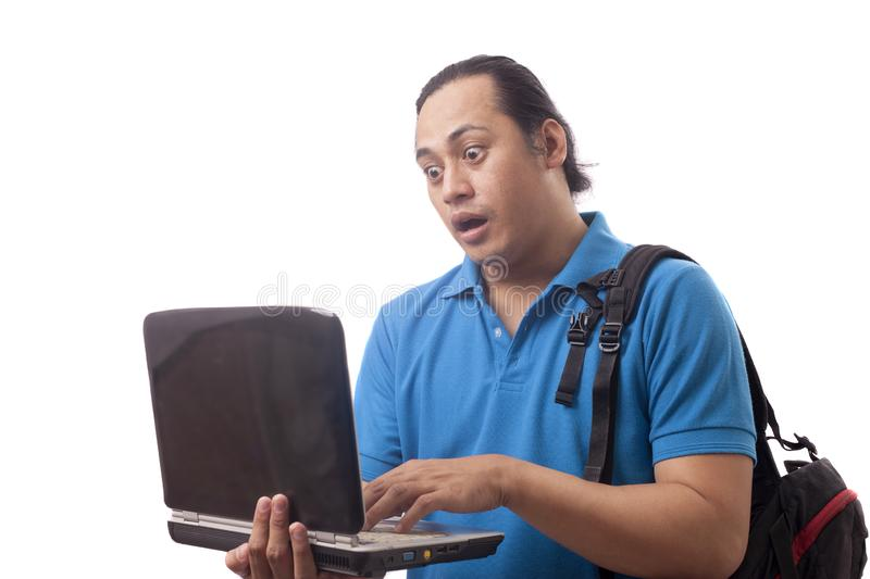 Young Man Gasping, Shocked Expression Looking at Laptop. Young Asian man student wearing blue shirt gasping, shocked expression looking at his laptop. Close up stock photo