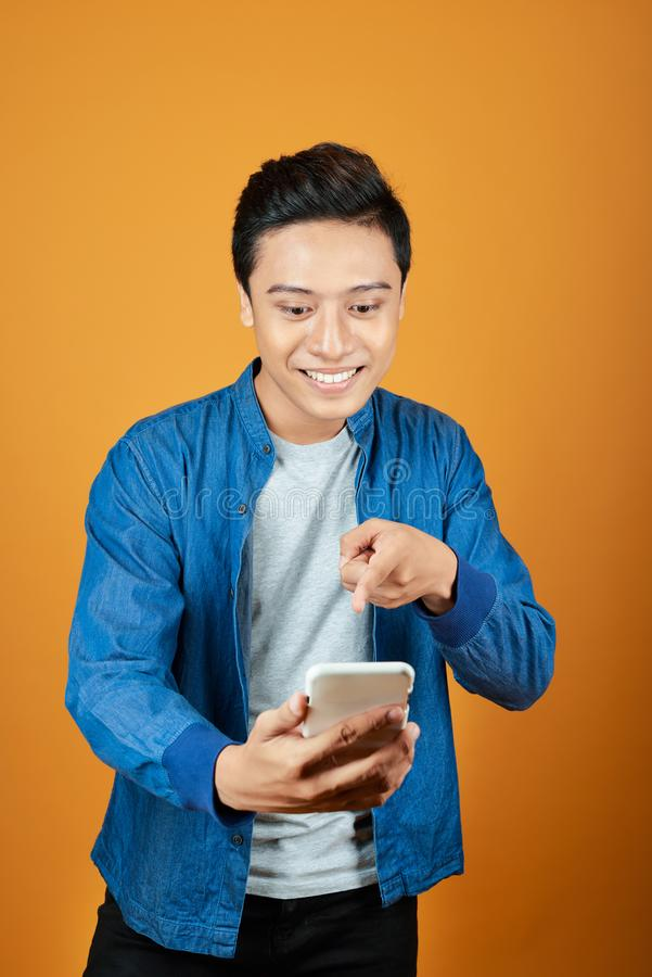 Young asian man surprised when he looking smartphone. On orange background royalty free stock photo