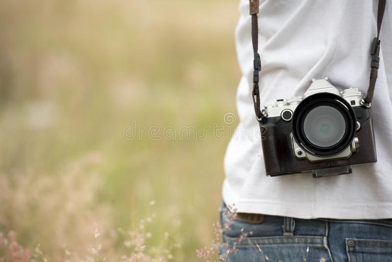 Young asian man taking photo outdoors with DSLR digital camera. Young cheerful female tourist having fun in coffee shop. royalty free stock photos