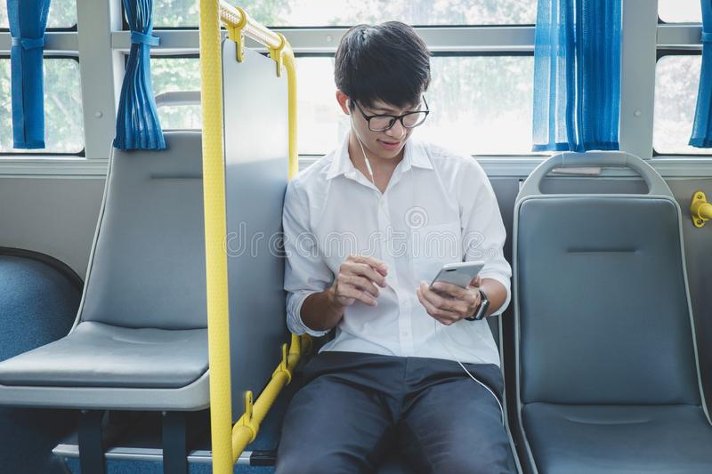 Young Asian man traveler sitting on a bus listening to music on smartphone while smile of happy, transport, tourism and road trip stock photos