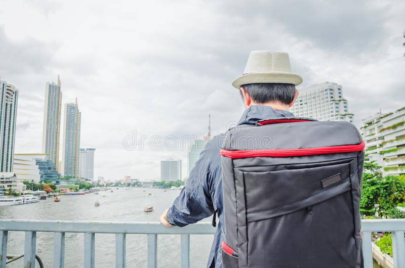 Young Asian man traveling backpacker in cityscape on Chao Phraya River in Bangkok, Thailand royalty free stock images