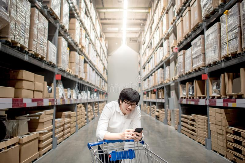 Young Asian man with trolley cart checking the shopping list in. Young Asian man standing with trolley cart checking the shopping list on his smartphone stock photo