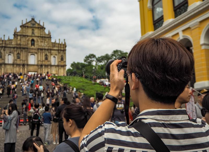 Young Asian man using a camera to take a picture of the Ruins of St. Paul`s in a large mass of royalty free stock photo