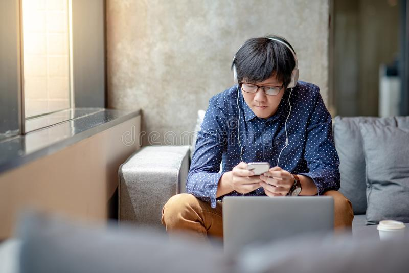 Young Asian man using smartphone relaxing on sofa royalty free stock photos