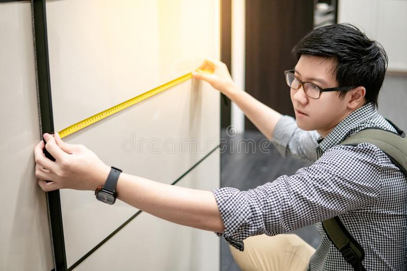 Asian man using tape measure on modern closet. Young Asian man using tape measure for measuring modern cabinet in walk-in closet showroom. Shopping furniture for royalty free stock photo