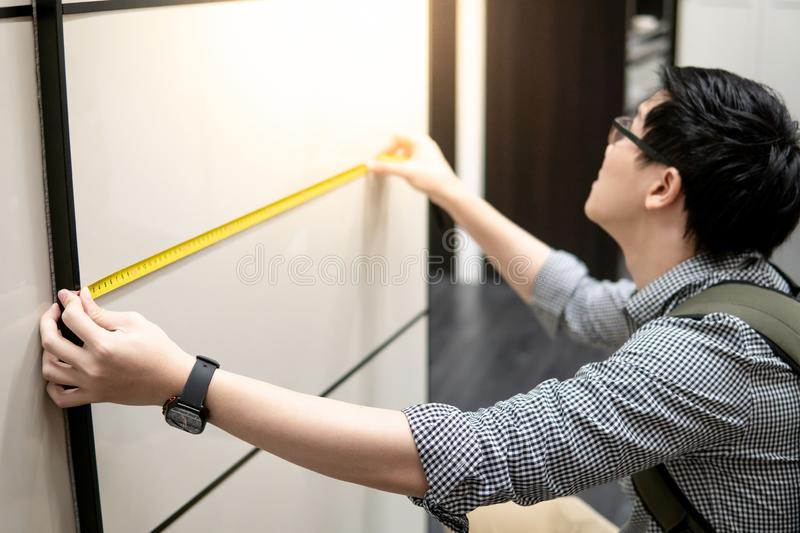 Asian man using tape measure on modern closet. Young Asian man using tape measure for measuring modern cabinet in walk-in closet showroom. Shopping furniture for stock image