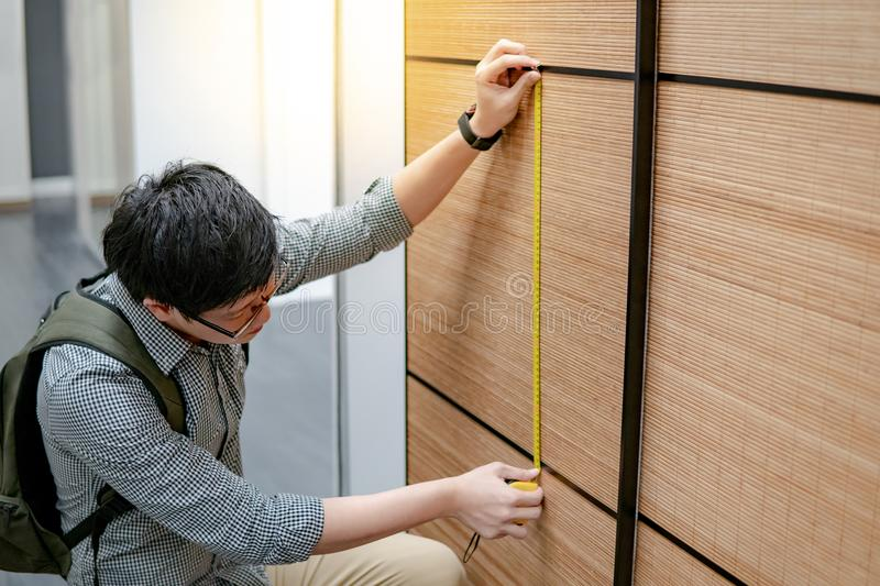 Asian man using tape measure on wooden closet. Young Asian man using tape measure for measuring modern wooden cabinet in walk-in closet showroom. Shopping royalty free stock photo