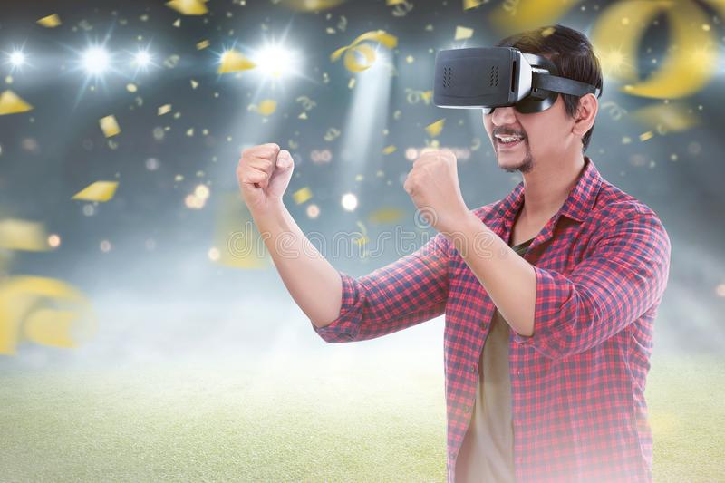Young asian man with virtual reality enjoying the football game. With confetti background stock photo