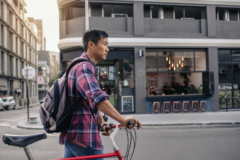 Young Asian man walking with his bike in the city royalty free stock image