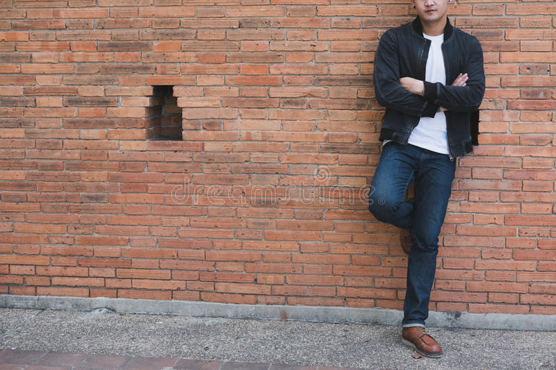 young asian man wearing black jacket and blue jeans standing against old orange brick wall stock photography