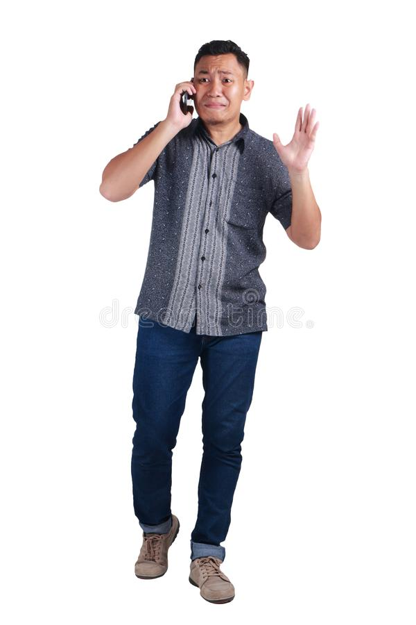 Young Man Talking at Phone, Cried Worried Expression. Young Asian man wearing blue jeans and batik shirt talking at phone, cried and worried expression. Isolated royalty free stock images