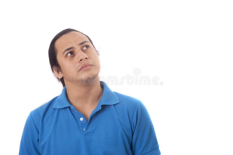 Funny Young Man Thinking Expression, Looking to The Side. Young Asian man wearing casual blue shirt thinking, looking to the side. Close up body portrait royalty free stock images