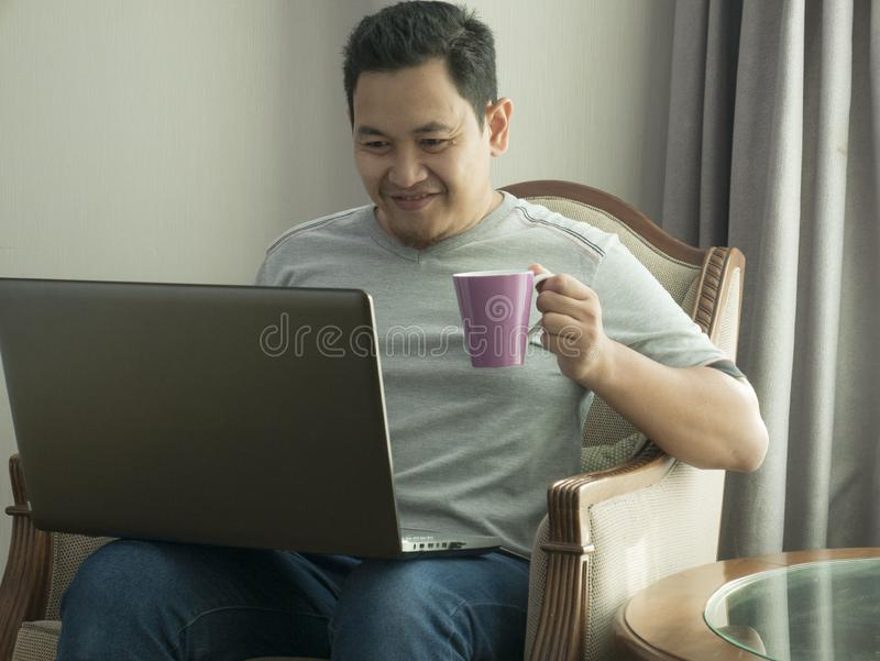 Young Man Working at Home on His Laptop, Smiling Expression stock photo
