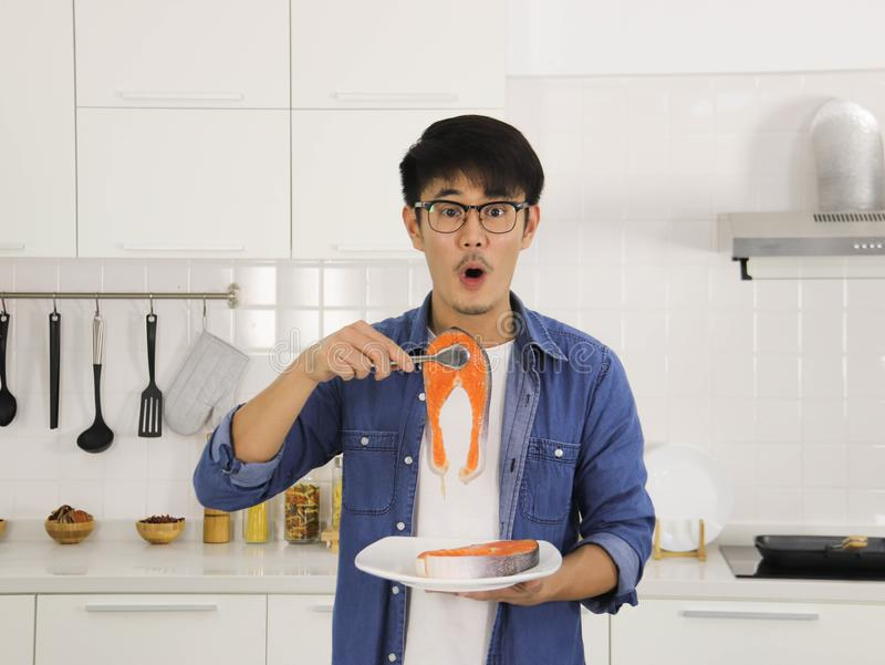 A man cooking salmon steak in the kitchen. Young Asian man wearing eye glasses tong a piece salmon fillet , making surprise face cooking salmon steak happily in stock images