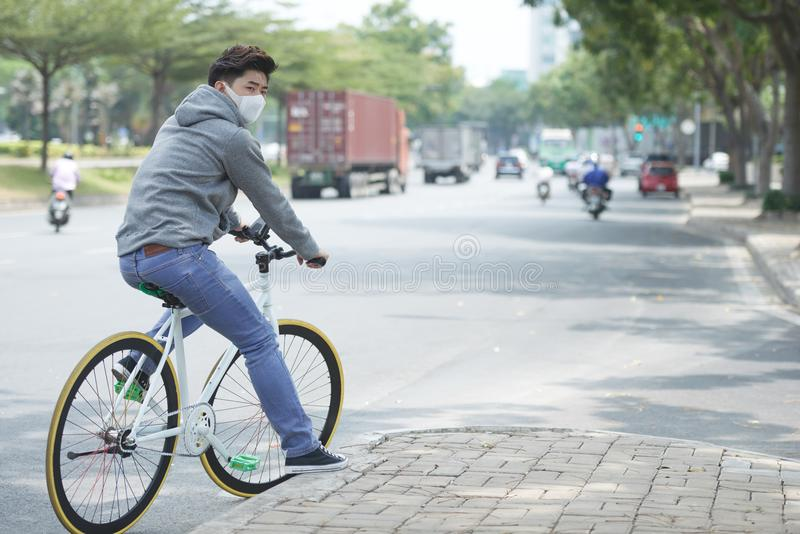 Suffering from air pollution. Young Asian man wearing face mask when cycling in polluted city royalty free stock photo