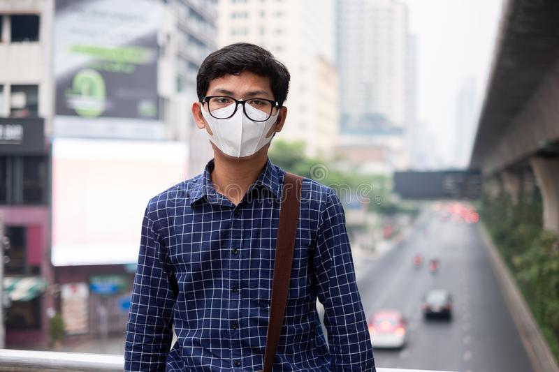 Young Asian man wearing N95 respiratory mask protect and filter pm2.5 particulate matter against traffic and dust city. Healthcare and air pollution concept stock photo