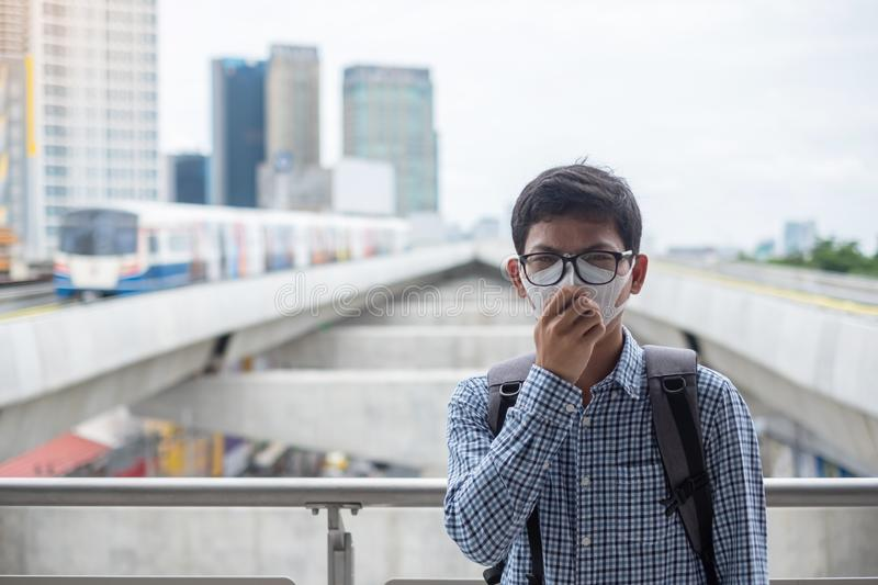 Young Asian man wearing N95 respiratory mask protect and filter pm2.5 particulate matter against traffic and dust city. Healthcare and air pollution concept royalty free stock images