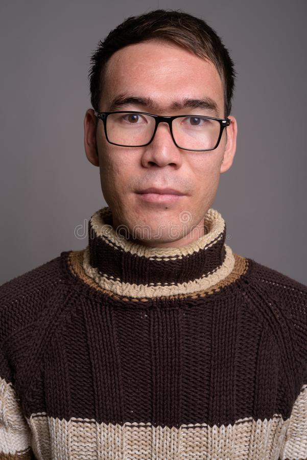 Young Asian man wearing turtleneck sweater against gray backgrou royalty free stock photo