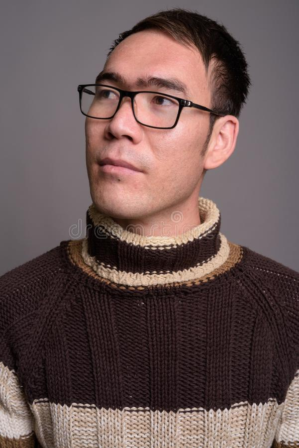 Young Asian man wearing turtleneck sweater against gray backgrou stock photo