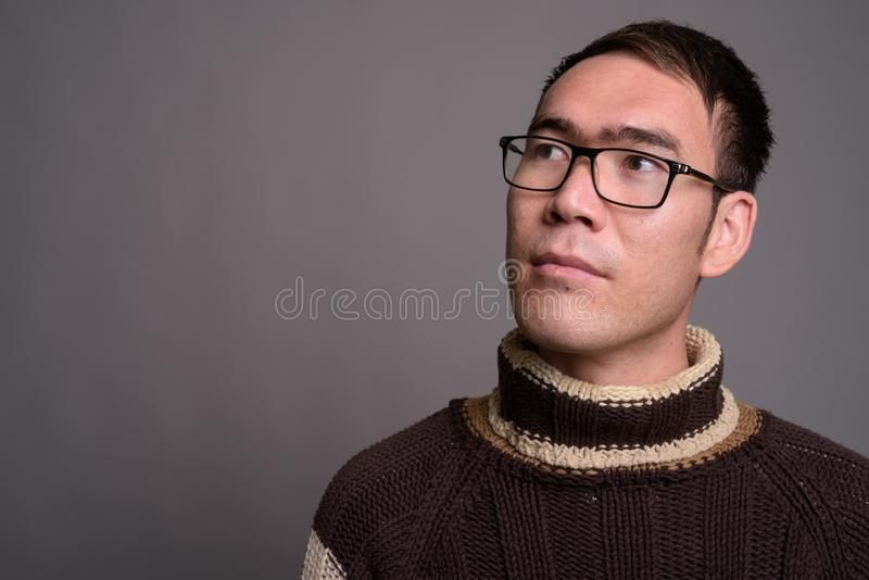 Young Asian man wearing turtleneck sweater against gray backgrou royalty free stock images