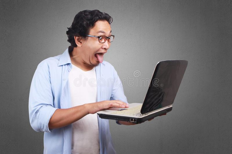 Young Man Take Out His Tounge, Funny Expression Looking at Laptoop royalty free stock image