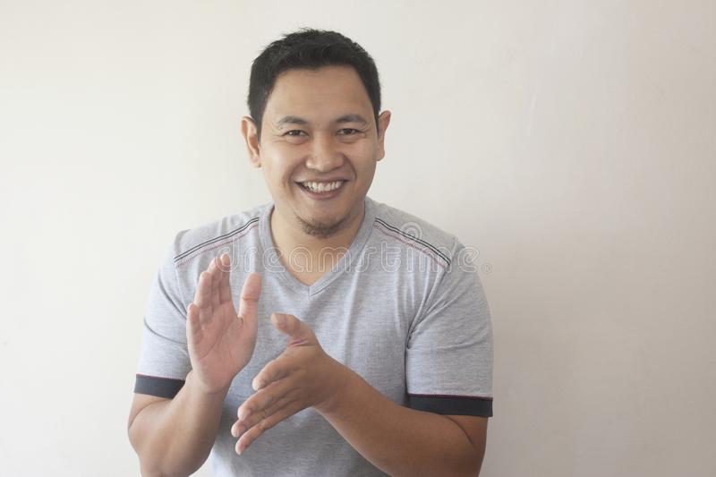 Happy Young Man Clapping Hands. Young Asian man wearing white shirt, happy proud clapping gesture.Over grey background, halfl body portrait adult handsome people stock photos
