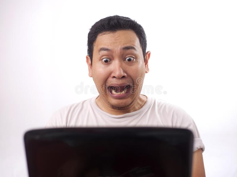 Young Man Screaming, Shocked Expression Looking at Laptop. Young Asian man wearing white shirt screaming, shocked expression looking at his laptop. Close up body royalty free stock photo