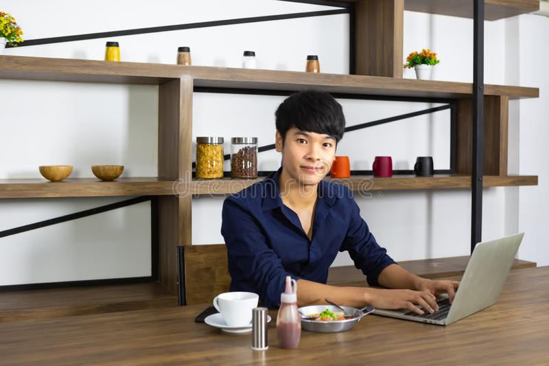 Young asian man working laptop with breakfast on wooden table royalty free stock photo