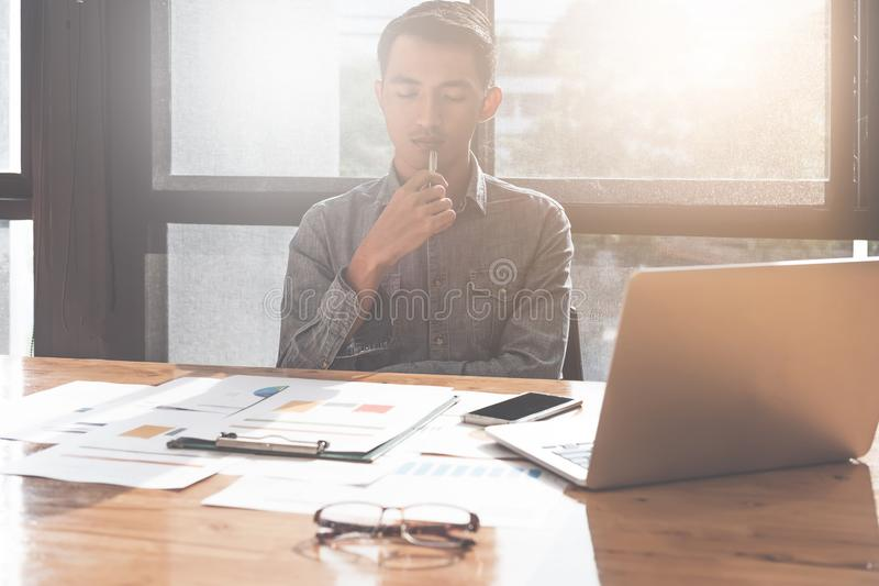 Young asian man working with laptop computer and document while royalty free stock photography
