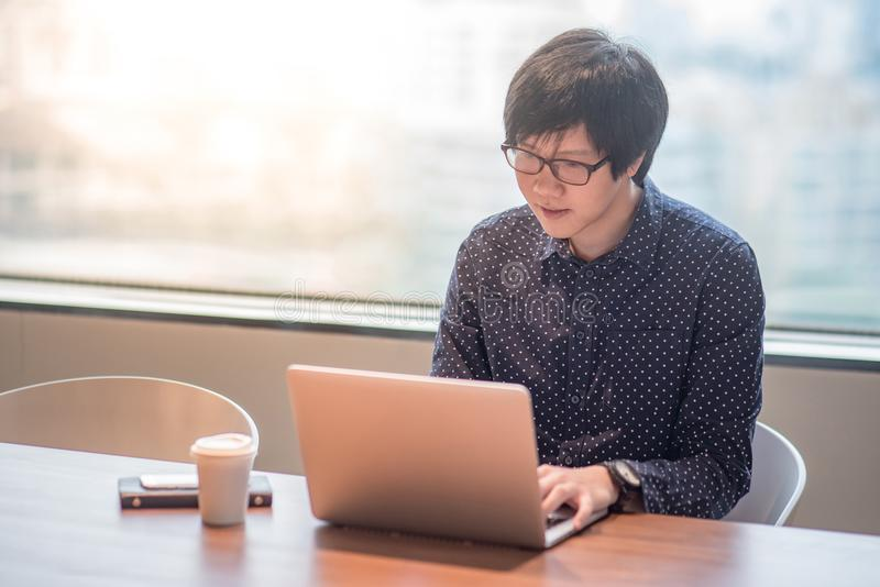 Young Asian man working with laptop computer in office. Young Asian businessman working with his laptop computer in office meeting room. entrepreneur and urban royalty free stock photography