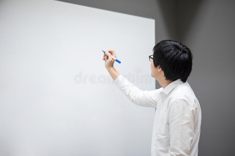 Young Asian man writing on white board in meeting room stock photos
