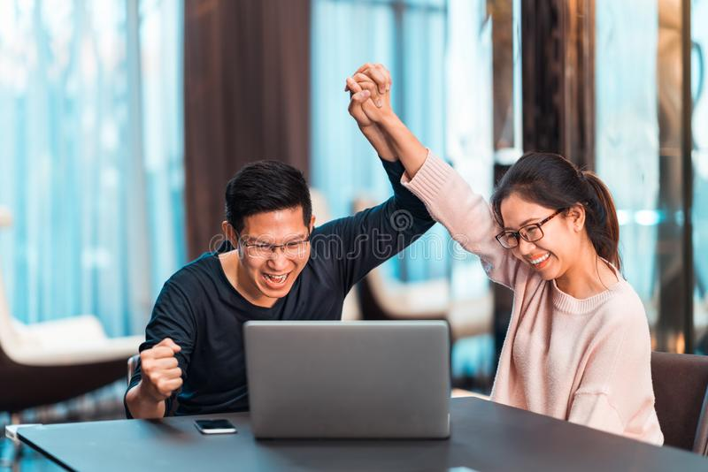 Young Asian married couple hold hands celebrating together, watching laptop computer in modern home office. Success job, love relationship, football sport royalty free stock photo