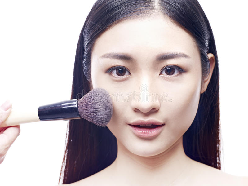 Young asian model applying foundation make-up. Make-up foundation being brushed on to face of a young and beautiful asian model, on white background royalty free stock photos