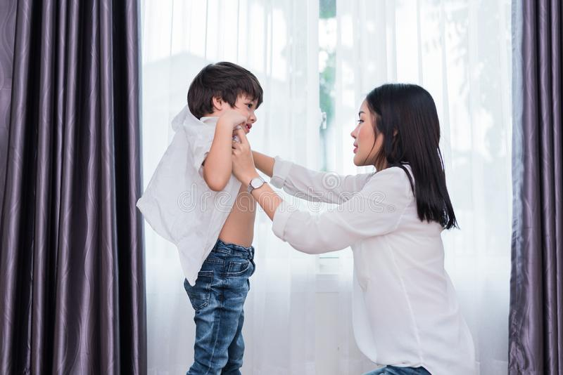 Young Asian mom dressed up son outfits for preparing go to school. Mother and son concept. Happy family and Home sweet home theme stock images