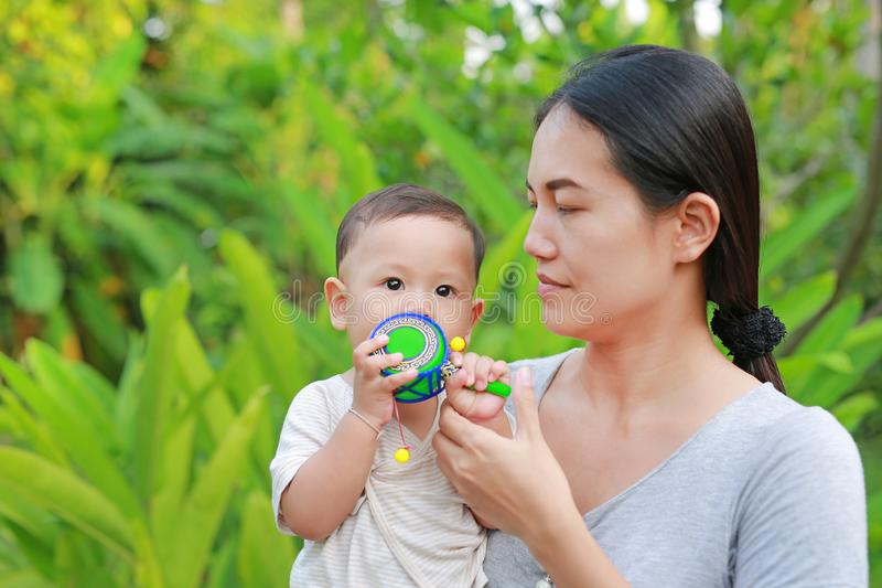 Young Asian mother carrying her baby boy and playing Pongapaeng toys Chinese Toy outdoors stock image