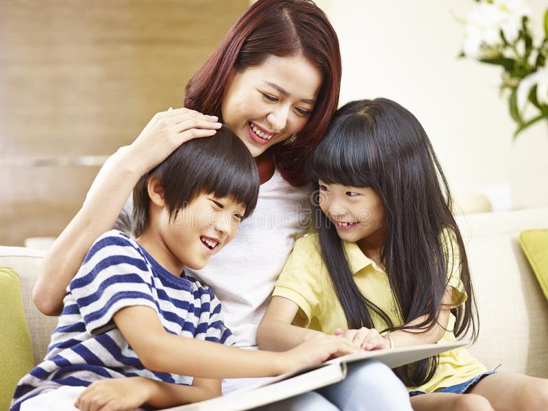 Asian mother reading story to two children stock images