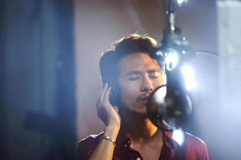 Young asian musician recording songs in studio. Young asian musician singer singing song in recording studio royalty free stock image