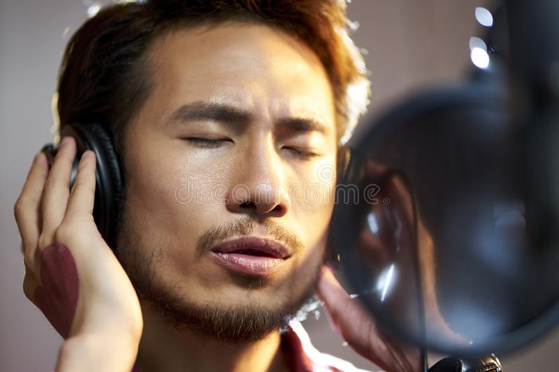 Young asian musician recording songs in studio. Young asian musician singer singing song in recording studio stock images