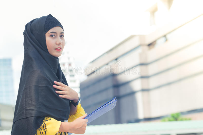 Young asian muslim business woman smiling and holding file document and standing at capital city. royalty free stock photography