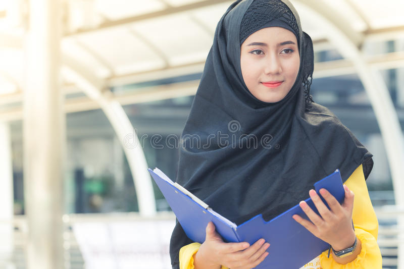 Young asian muslim business woman smiling and holding file document and standing at capital city. stock photo
