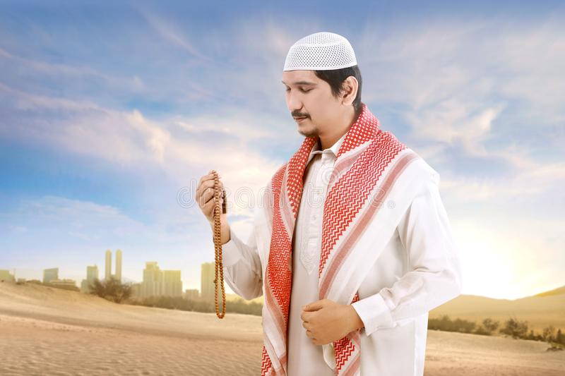 Young asian muslim man with cap and turban standing and praying with prayer beads on the sand. With blue sky background stock photo