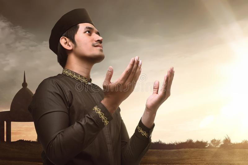 Young asian muslim man raising hand and praying royalty free stock photos