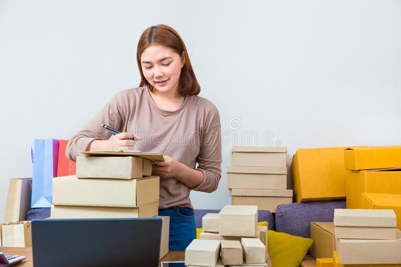 Young asian online seller businesswoman working from home writing down her customer names on her notepad and surrounded by boxes. Of her products, good for stock photos