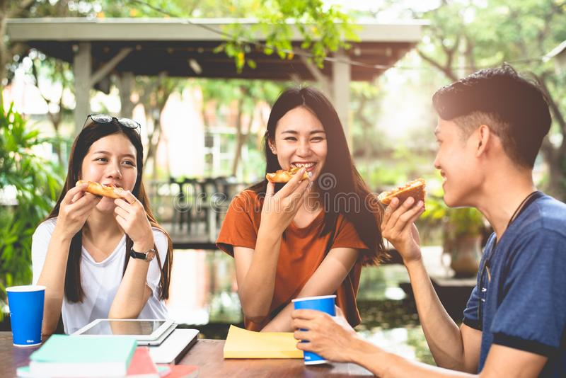 Young Asian people eating pizza together by hands. Food and Friendship celebration party concept. Lifestyles and people in theme. Happiness of enjoy life of royalty free stock photos
