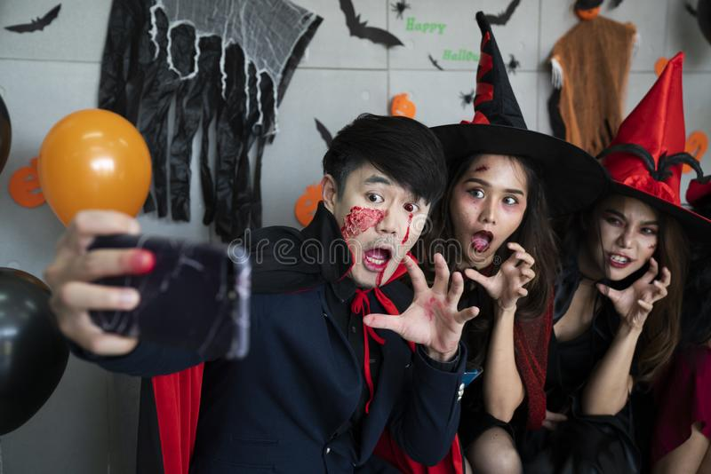 Young Asian people, a group of three persons, in scary costumes selfie their own photo. Group of friends having fun at a party royalty free stock images