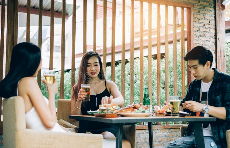 Young asian people having fun at drinking with cheering with beer at restaurant stock photography