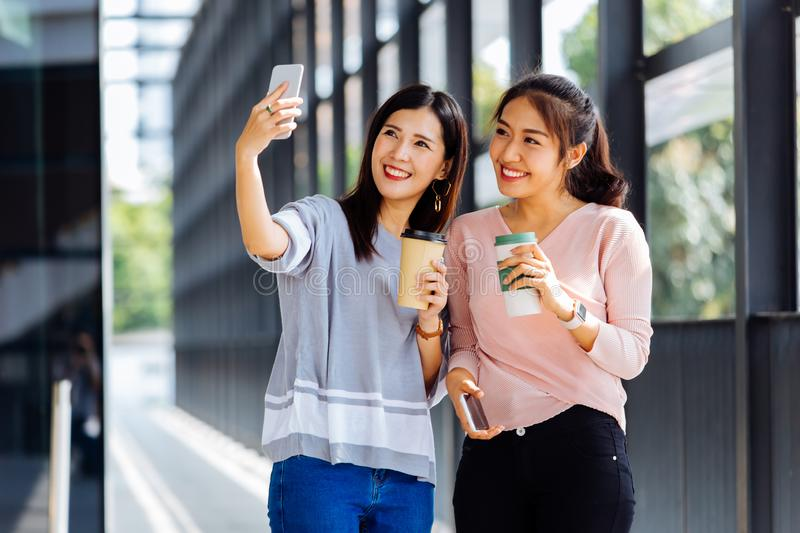 Young Asian people taking selfie photos together inside the glass building stock images